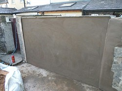Gates removed from yard opening following house flooding, built solid wall, render and cap . Prevents further flooding