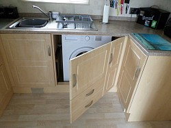 Secret door and removable plinth modifications to house washing machine in static caravan